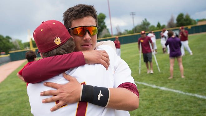 Alex Gonzales and Brendan Paul of Rocky Mountain High School share a hug after a 9-4 loss to Cherokee Trail in the state championship series at All City Field in Denver Sunday.