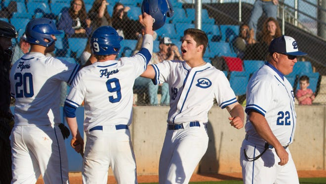 Dixie's Tyson Fisher (second from right) celebrates a home run against Desert Hills on Tuesday, March 4, 2017.