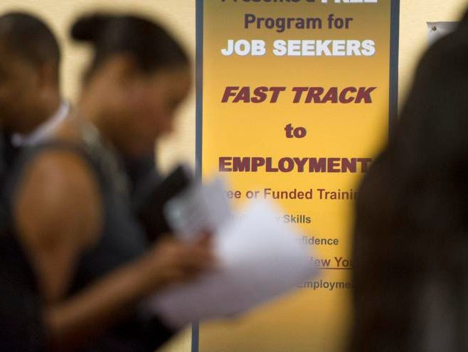 In this May 30 photo, job seekers line up to talk to recruiters during a job fair held in Atlanta. The number of people seeking U.S. unemployment benefits dropped 12,000 to a seasonally adjusted 350,000 last week, though the total was elevated for the third straight week by technical problems in California.