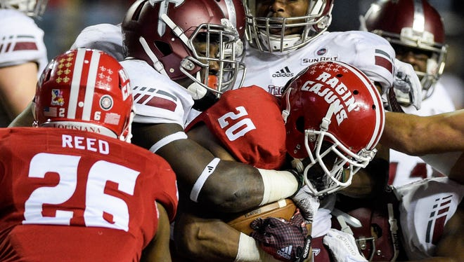 UL Ragin' Cajuns wide receiver Gary Haynes (20) is stifled   by a host of Troy Trojans defensive players on a run during the second half of an NCAA football game against the Troy Trojans at Cajun Field in Lafayette, La., Saturday, Dec. 5, 2015.