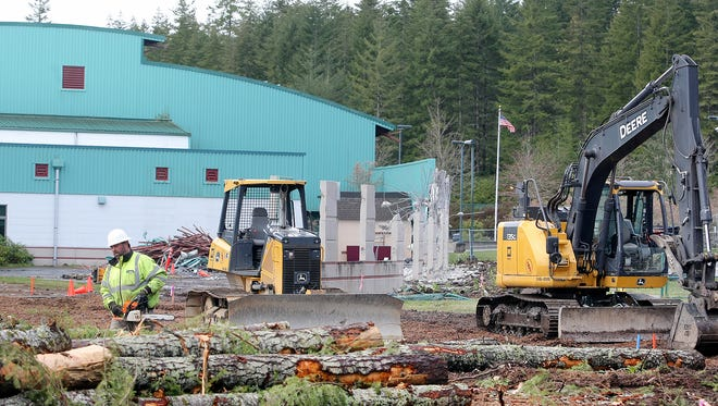 Timber is cut to make room for a school bus lane at Klahowya Secondary School. A wall in the background has already been taken down. New classrooms, an auxiliary gym and a music room are being added.