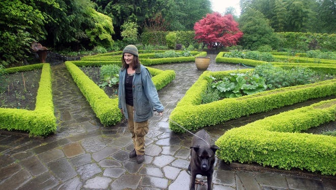 Ceclia Pedersen and her dog Corbie stand in a garden at Heronswood in North Kitsap, now owned and operated by the Port Gamble S'Kallam Tribe. The garden is open Mother's Day weekend for its spring plant sale.