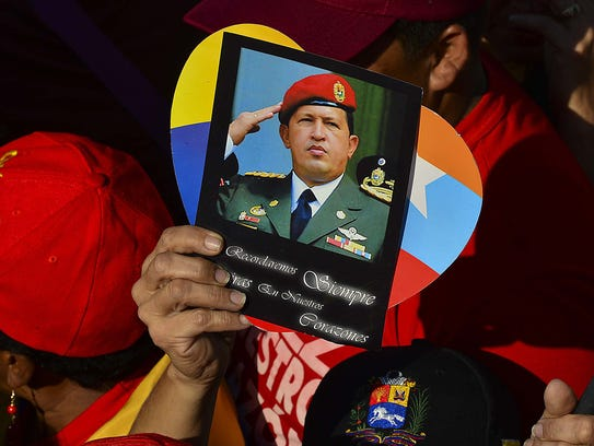 A supporter holds a picture of the late Venezuelan