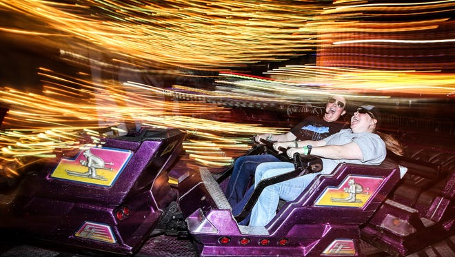 """Sisters Carrie Ernst, 22, left, and Sammie Ernst, 19, laugh as they take laps at high speeds on The Matterhorn ride at the Kentucky State Fair on Tuesday evening. """"I like all of the different rides you don't normally see at other amusement parks,"""" Sammie said. Aug. 25, 2015"""