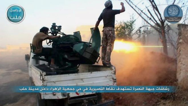 In this image posted on the Twitter page of Syria's al-Qaeda-linked Nusra Front on July 7, 2015, fighters from the Nusra Front fire their weapons against the Syrian government forces at the western Zahra neighborhood in Aleppo, Syria.