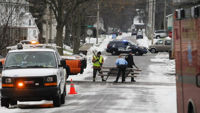 Emergency personnel and Consumers Energy workers near the scene of a gas leak near the corner S. Cedar and Isbell streets Dec. 31.  Nearby residents were evacuated for a short time while the gas leak was fixed.