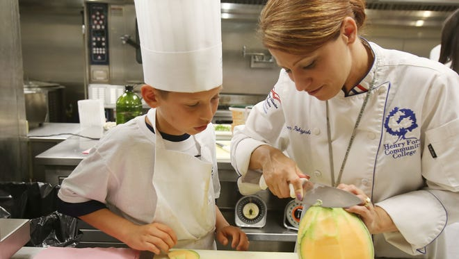 Henry Ford Community College chef instructor Karen Pokrywki shows  camper  Zachary Fenbert 10, of Maybee how to  cut a cantaloupe at Henry Ford Community College's first culinary kids camp in Dearborn on Monday, June 15, 2015.