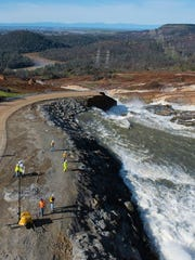 Water from the Oroville Dam auxiliary spillway at Lake Oroville about 150 miles northwest of San Francisco erodes the roadway Feb. 12, 2017, just below the emergency spillway.