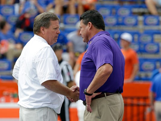 Florida head coach Jim McElwain, left, and LSU head coach Ed Orgeron shake hands at midfield before an NCAA college football game, Saturday, Oct. 7, 2017, in Gainesville, Fla. (AP Photo/John Raoux)
