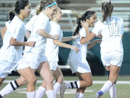 Abilene High players celebrate with Gabby Valero, second