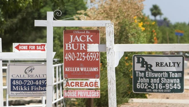 Homes sales have slowed in metro Phoenix, but the number of houses for sale is climbing. A corner in Gilbert with three signs for nearby properties.