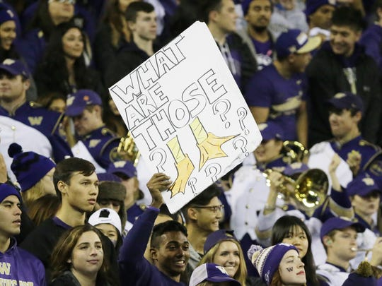 """A Washington fan holds a sign with the pop-culture internet viral-video phrase """"What are those???"""" with a drawing of duck feet during an NCAA college football game between Washington and the Oregon Ducks, Saturday, Oct. 17, 2015, in Seattle. Oregon beat Washington 26-20. (AP Photo/Ted S. Warren)"""