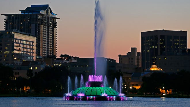 Water rises from a fountain on Lake Eola as the sun sets in Orlando.