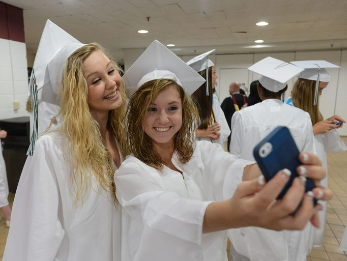 Reilly Mason, left, and Katie Briddell take a selfie at Parkside High School graduation Thursday at the Wicomico Youth & Civic Center in Salisbury.