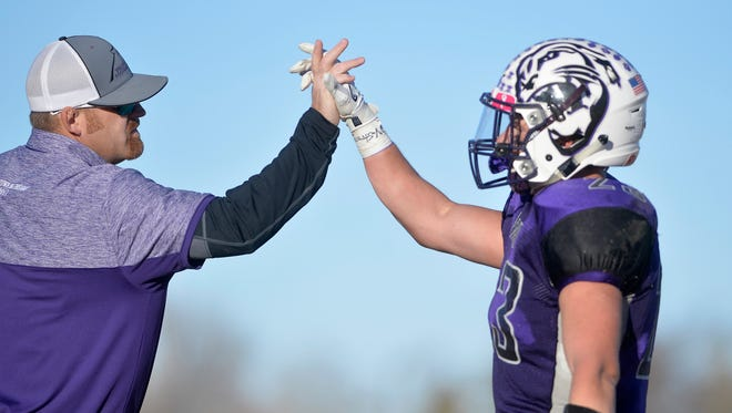 Eric Watson, left, high-fives Trever VandenBos during  Valier's semifinal game against Westby-Grenora last November. Watson recently resigned as the Panthers' head football coach.