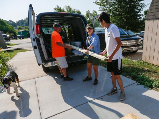 SPS students Dalton Ragsdale, right, and Lily Kirch along with their teacher Howard Zeigenbein unload 2x8 pieces of lumber at the Habitat for Humanity site at Legacy Court on Friday, June 15, 2018.