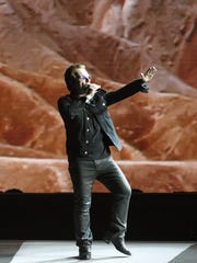 U2's lead singer Bono performs on stage during their