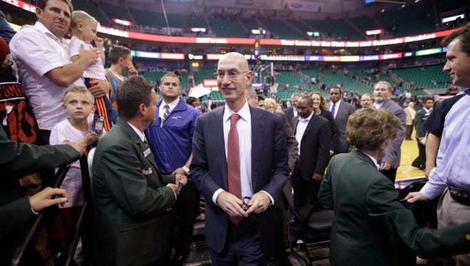 NBA commissioner Adam Silver walks off the court following a basketball game.