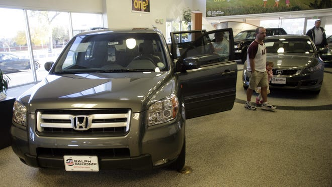 Buyers look over a 2008 Pilot sports-utility vehicle  at a Honda dealership in the south Denver suburb of Littleton, Colo., in this Oct. 18, 2007, file photo. Honda is adding nearly 105,000 vehicles to its U.S. recall of driver's side air bag inflators that can explode with too much force.
