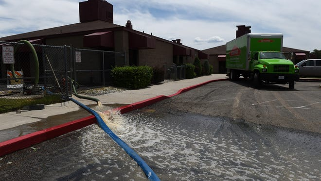 Water is pumped away from the building after a flash flood inundates Whitehead Elementary in Sparks.