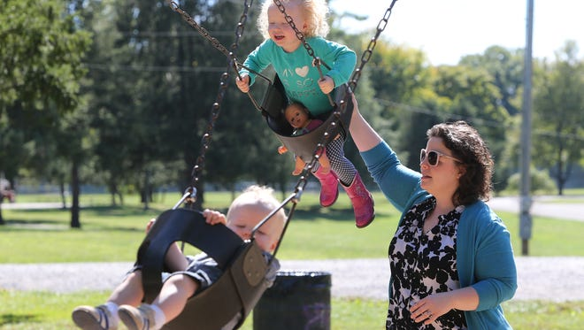 Rebecca Mercer, a doula, pushes her son, Jason, 1, and daughter, Ava, 3, on swings at Joe Creason Park.