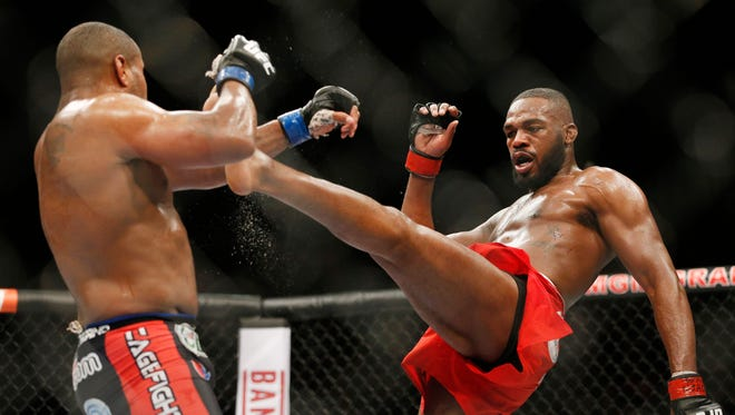 Jon Jones kicks Daniel Cormier during their light heavyweight title bout at UFC 182.