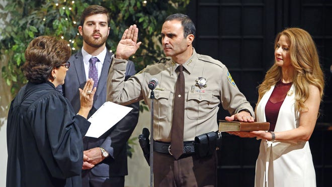 Maricopa County Sheriff Paul Penzone takes the oath of office from U.S. Judge Mary Murguia of the 9th Circuit of Appeals as his son, Austin, and wife, Veronica, look on Jan. 4, 2017, at the Heard Museum in Phoenix.
