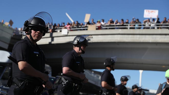 Police officers monitor protesters during a demonstration against the travel ban that was imposed by President Trump at Los Angeles International Airport on Jan. 29, 2017.