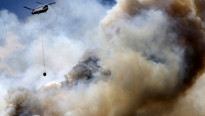 In this Saturday, June 9, 2018, photo, helicopter works the wildfire on the east side of Hermosa Cliffs near Hermosa, Colo.