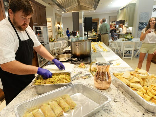 Chef Blake Jackson cooks for the Society of the Golden Fork Dinner at the Kitchen and Bath Cottage Friday evening.