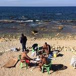 ARCHIVO - En esta fotografía de archivo del 9 de febrero de 2016, libaneses juegan cartas y fuman pipas de agua mientras se asolean en un inusualmente caliente clima en Corniche, Beirut, Líbano, en el mar Mediterráneo.