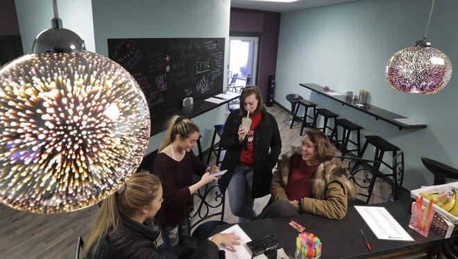 Kimberly High School student Klaire Kulas, center, drinks a shake while talking with her friends Jada Smith, left, Elizabeth Peters and Kate Wydeven at Exquisite Force Salon and Fitness in Kimberly.