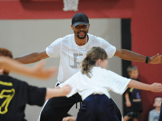 Former Wolf Pack basketball player Ramon Sessions leads children in some drills during his youth basketball camp in Reno in 2012.