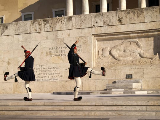 Members of the Evzoni presidential guard perform the changing of the guard ceremony in front of the tomb of the unknown soldier at Syntagma Square in Athens.