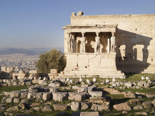 The Erechtheion, an ancient Greek temple on the north side of the Acropolis of Athens, is seen with the city as a backdrop.