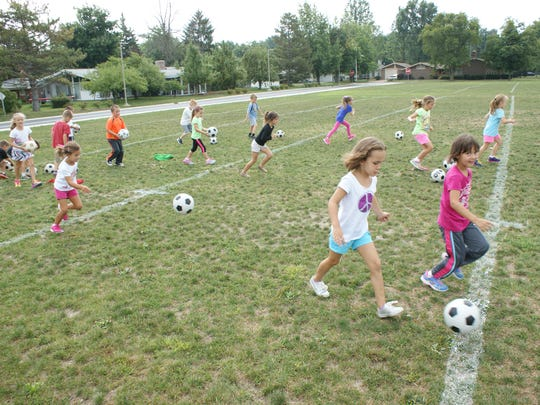 Students in physical education work on kicking soccer balls down field to develop motor skills