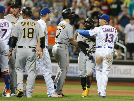 Pittsburgh Pirates second baseman Josh Harrison (5) is restrained by New York Mets second baseman Asdrubal Cabrera (13) during a benches clearing incident during the eighth inning at Citi Field.