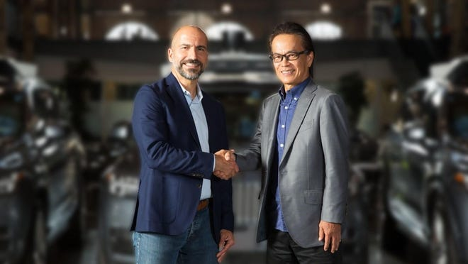 Dara Khosrowshahi, Uber's CEO, Shigeki Tomoyama, executive vice president, TMC, and president, Toyota Connected Company shake hands on the agreement to collaborate with the aim of advancing and bringing to market autonomous ride-sharing as a mobility service at scale.