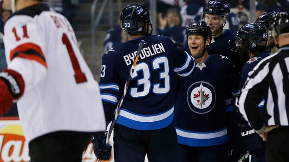 Winnipeg Jets' Dustin Byfuglien (33), Matt Hendricks (15), Tyler Myers (57) and Mathieu Perreault (85) celebrate Hendricks' goal against New Jersey Devils' Brian Boyle (11) during the second period of an NHL hockey game in Winnipeg, Manitoba, Saturday, Nov. 18, 2017. (John Woods/The Canadian Press via AP)