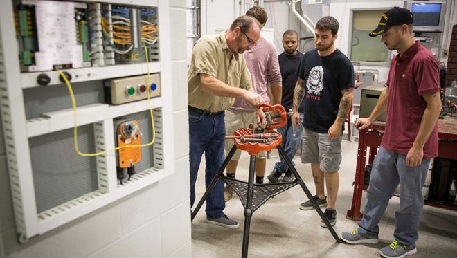 Ivy Tech Professor Gary Grider helps student work through a problem in HVAC repair during one of the courses at the school. Ivy Tech caters not only to recent high school graduates and people who want job retraining to recapture past jobs but also people who are working but want to improve their job skills for other jobs.