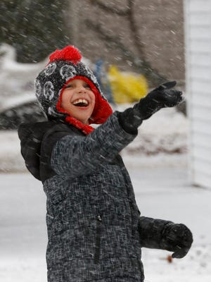 Mason Lynd, 8, of Weston, plays with the snow falling Wednesday at his house.