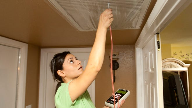 Elena Chrimat of Ideal Energy tests if a house has air leaks during an APS home-energy audit Friday, May 11, 2012.