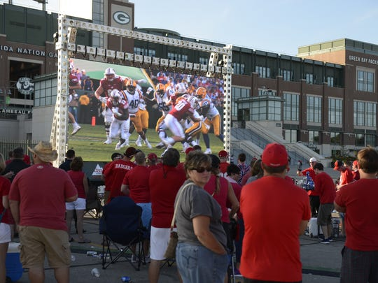Wisconsin Badgers fans watch the game against LSU on a big screen outside Lambeau Field on Sept. 3.
