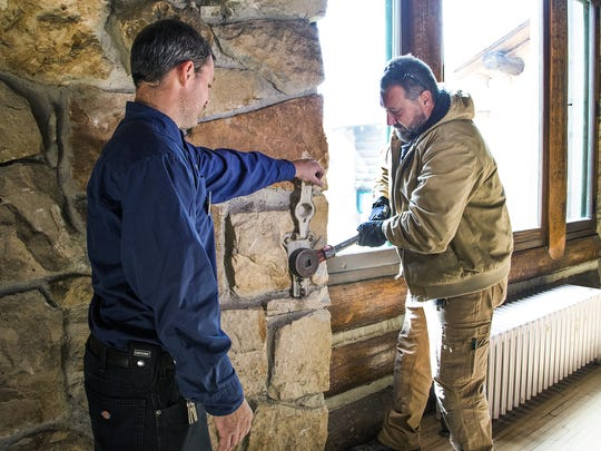 Maintenance workers Jerohm Faust, left, and Mark Pastir use a hand crank to lower the shutters as the Grand Canyon Lodge at the North Rim is prepared for it's annual winter closure.