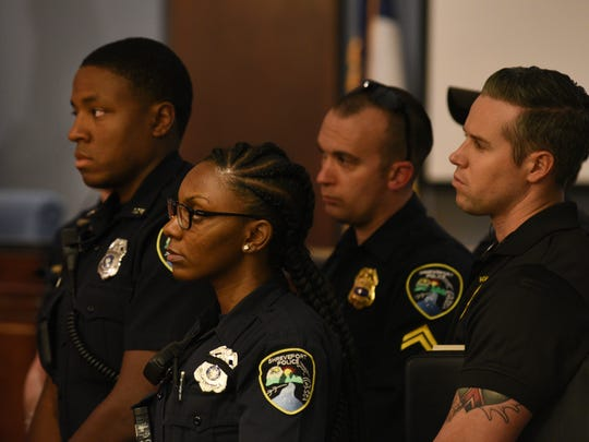 Shreveport police officers listen to SPD Chief Alan Crump speak at a press conference addressing the recent spike in gun violence.