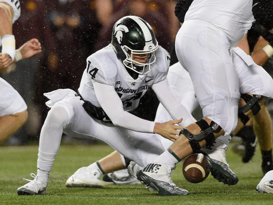 Brian Lewerke #14 of the Michigan State Spartans fumbles