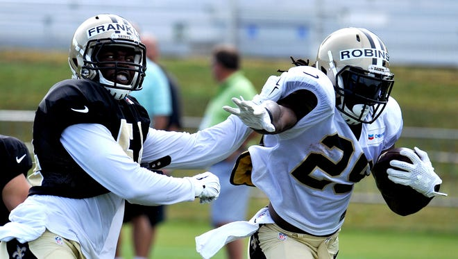 New Orleans Saints running back Khiry Robinson (29) tries to run around linebacker Jerry Franklin (54) during the team's NFL football training camp in White Sulphur Springs, W. Va., Sunday, Aug. 2, 2015. (AP Photo/Chris Tilley)