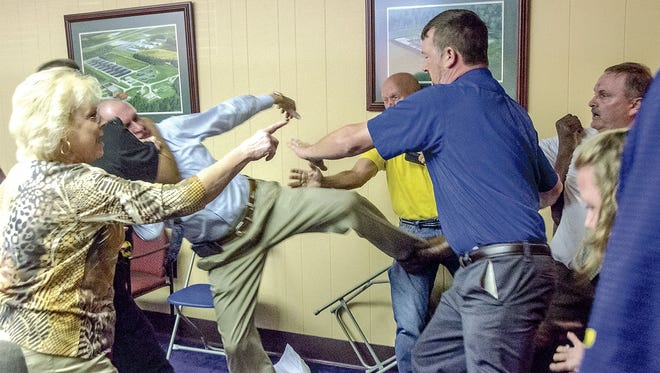 Alexander City Mayor Charles Shaw, left, is restrained by an officer after a fight broke out between him and councilman Tony Goss, far right, during a meeting of the Alexander City City Council in Alexander City, Ala. on Monday, April 25, 2016. Those attending the meeting along with officers had to intervene after the meeting adjourned. The incident took place at Alexander City City Hall and was intended to discuss city audits and other municipal financial issues but the meeting broke down to a shouting match before it ended and the brawl ensued. (Mitch Sneed/Alexander City Outlook via AP)