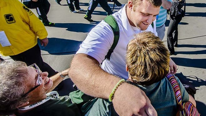 Jack Allen (top) of MSU hugs his aunt Diana Culver (right) while his grandmother Sharon Slinkman (left) smiles as the MSU football team walks into the Rose Bowl prior to the 2014 Rose Bowl in 2014 in Pasadena, California.