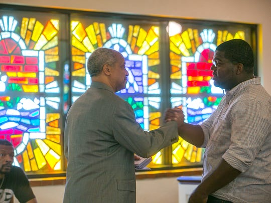 The Rev. Dr. Benjamin Thomas Sr. (middle) shakes hands with the Rev. Reginald D. Walton after a prayer service at Historic Tanner Chapel AME Church in Phoenix on Thursday, June 18, 2015.